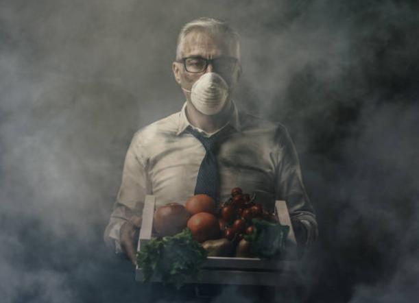 мъж с маска, щайга с плодове и зеленчуци, дим